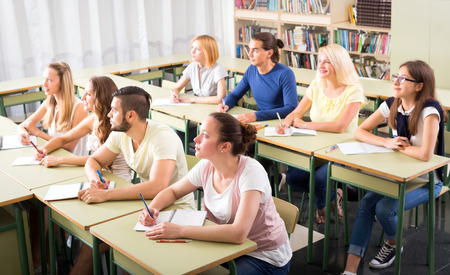 finding a mate: Students in university classroom are sitting at their desks and looking forward at professor Stock Photo