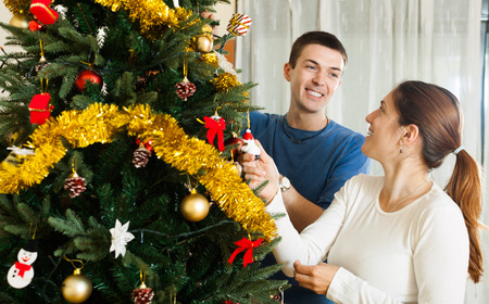 home decorating: Adult couple decorating Christmas tree in home