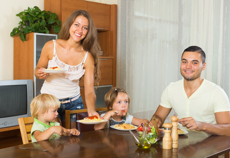 gladful: happy family of four  having lunch with  italian pasta at home together