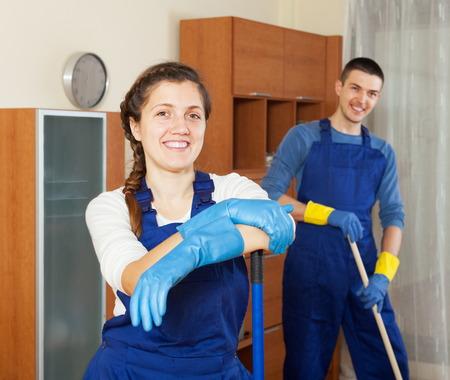 houseman: Happy cleaners team cleaning floor in room Stock Photo