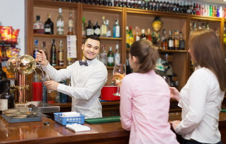 Two girls flirting with smiling handsome barman at bar