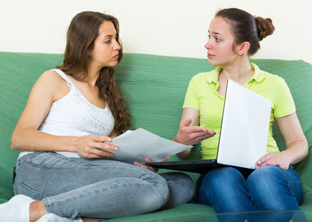 wistful: Two upset girls with financial documents and laptop sitting on sofa at home