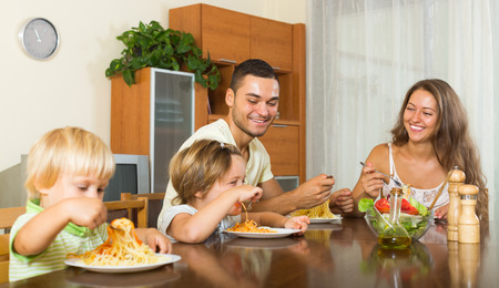 young  family: happy family of four people  having lunch with pasta at home together