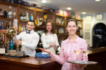 bartenders: Young waitress holding tray with glasses, bartenders at the distance Stock Photo