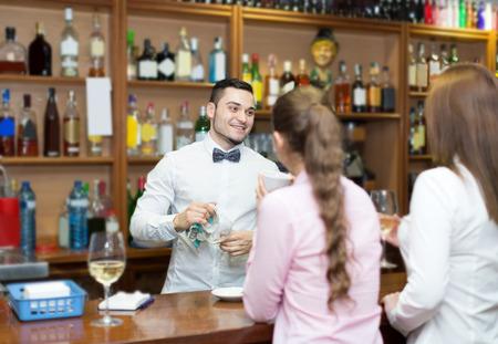 barmen: Young bartender and smiling women at bar