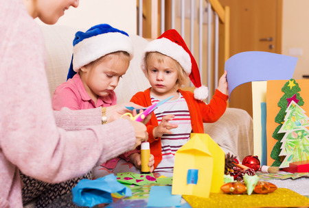 4s: woman with two girls preparing for Christmas at home