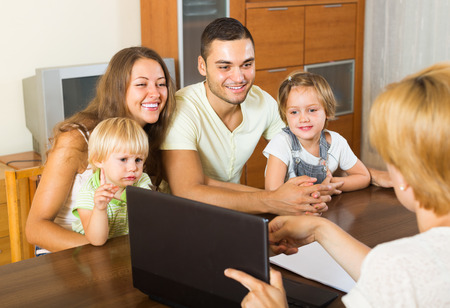 Insurance agent consulting smiling young family with kids at home. Focus on woman