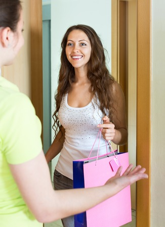neighbours: Young woman congratulating her friend and gives a gift