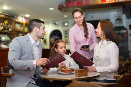 Smiling waitress serving family of three at cafe table. Selective focus on guy 写真素材