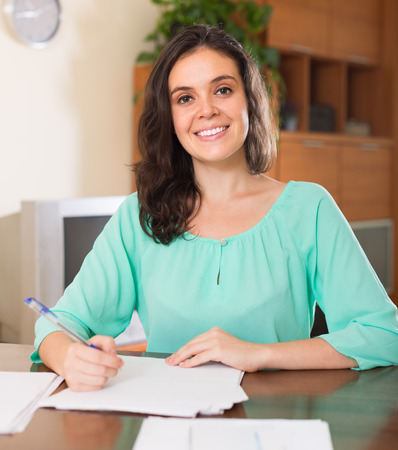 parsimony: Happy brunette long-haired woman fills in the questionnaire at home interior Stock Photo