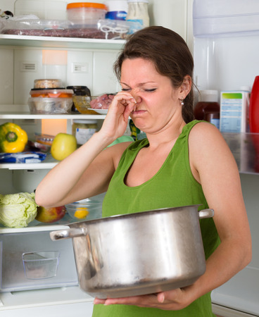 frowy: Young woman holding foul food near refrigerator at home kitchen Stock Photo