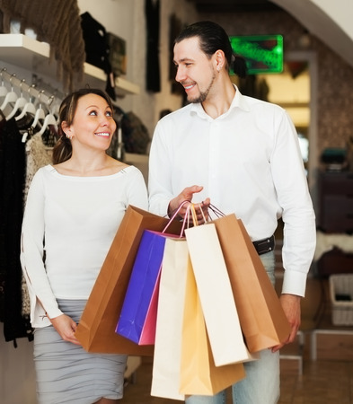 family shopping: Family with shopping bags at clothing boutique