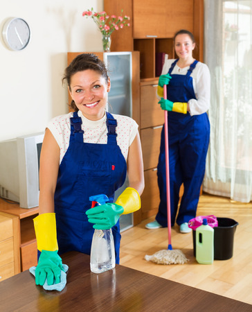 empleada domestica: Smiling professional cleaners washing apartment with rag and mop