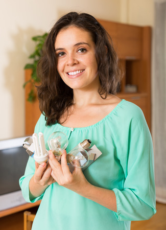 armful: Smiling young long-haired woman with armful of lightbulbs at home