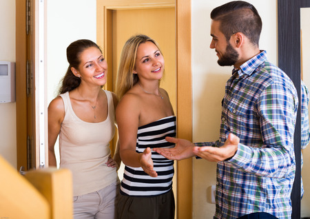 a marriage meeting: Smiling girls visiting male friend at his new apartment Stock Photo