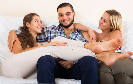 polygamy: Portrait of two smiling charming girls with attractive boyfriend