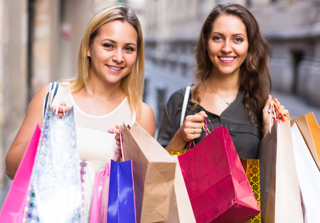 spendthrift: Two joyful young women holding many bags after shopping