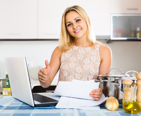 advantaged: american blonde female signing documents at the kitchen Stock Photo