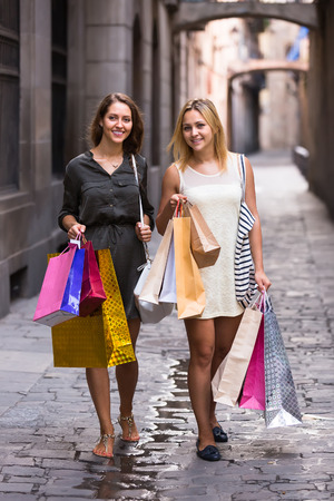 spendthrift: Two happy smiling girls walking by street with shopping bags