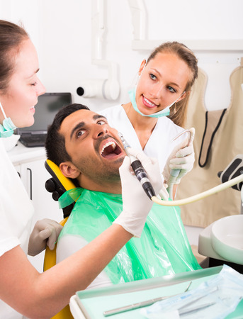 oral cavity: Female dentist with assistant diagnostics the oral cavity of male patient at clinic Stock Photo