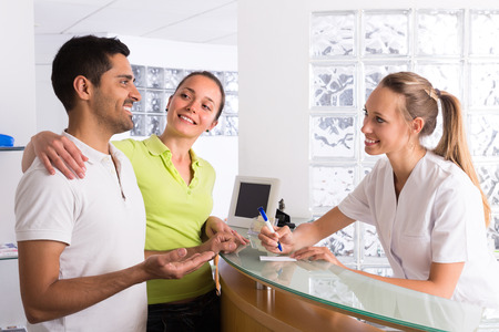 recepci�n: Positive young couple talking with smiling secretary at reception in the clinic