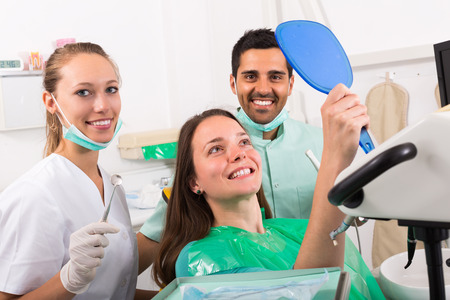 contented: Smiling dentist with assistant and contented patient at dental clinic Stock Photo