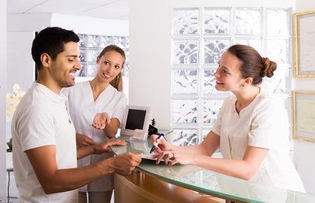 recepcionista: Hombre joven positivo que habla con el personal de enfermería en el consultorio médico
