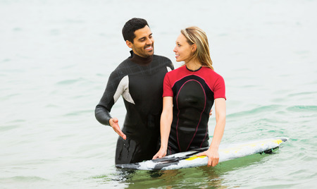 waist deep: two adults surfers couple waist deep in sea water