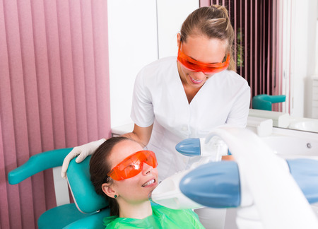 teeth: Woman patient at teeth whitening procedure in the dental clinic