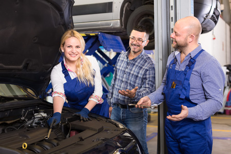 job satisfaction: Happy female mechanic repairing a car with a wrench while her male colleague and owner are consulting her Stock Photo