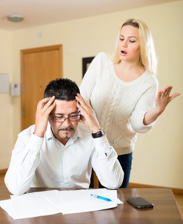 frugality: Heterosexual couple arguing because of financial difficulties