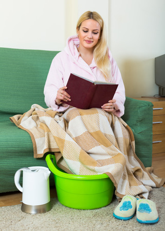 woman bathrobe: Young blonde taking foot bath and reading book on sofa Stock Photo