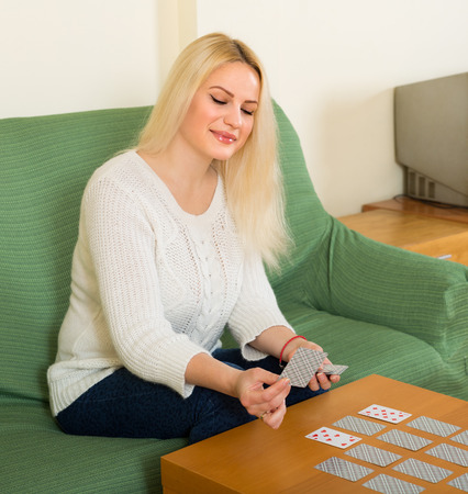 predictor: Young smiling woman playing solitaire at domestic interior Stock Photo