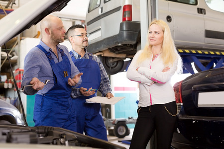 specialists: Smiling young girl talking with specialists at auto repair shop. Focus on the left man Stock Photo
