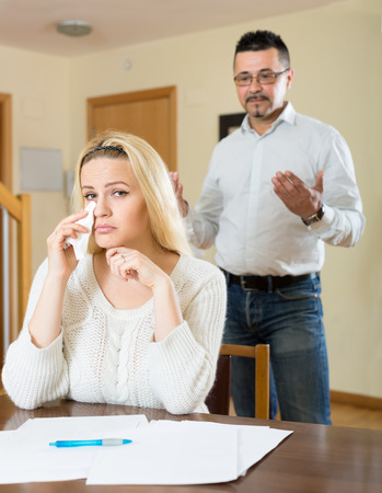 desperately: Couple having a quarell over financial problems. Wife is sitting at the table crying desperately while her husband is standing behind