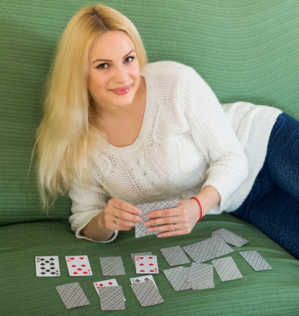 Young smiling blonde girl playing solitaire on sofa at home Stock Photo