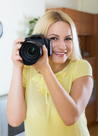 25s: Female smiling photographer testing new camera at home Stock Photo