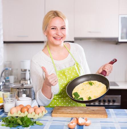 omlet: Smiling woman  making omlet in  kitchen Stock Photo