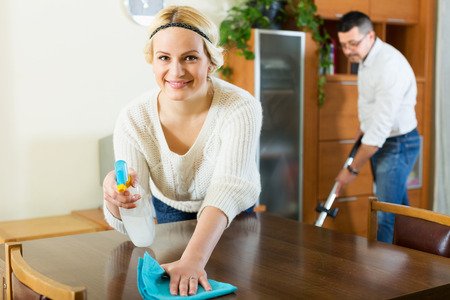dusting: Happy spouses dusting and hoovering at domestic interior