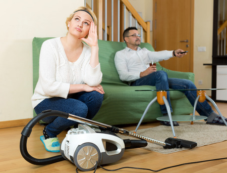 tidying up: Tired woman tidying up, husband relaxing on couch