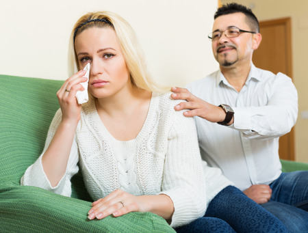 fracas: Man asking for forgiveness from sad woman after quarrel at home. Focus on girl