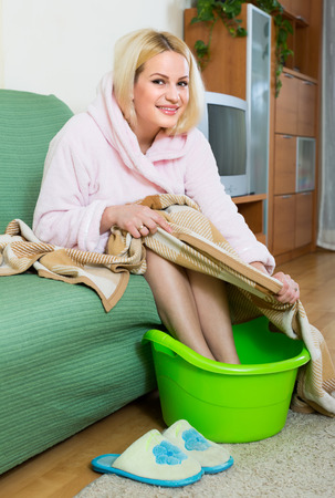 footcare: Young blonde woman taking foot bath on sofa at home Stock Photo