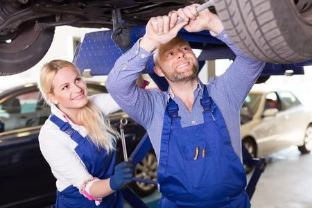 crew: Auto service center crew repairing a broken car