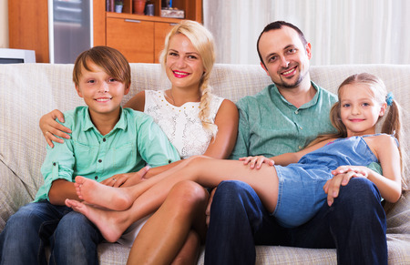 clase media: Portrait of smiling middle class family with two children at home interior. Focus on woman Foto de archivo