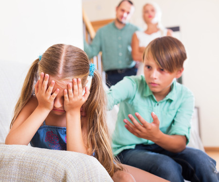 abusing: Little sister and brother abusing each other, a parents standing near them at home