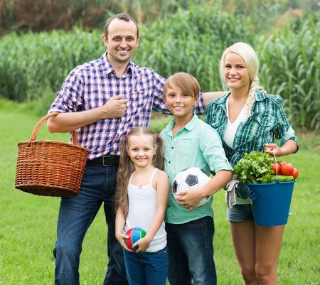 familia pic nic: Familia feliz de fin de semana de verano de cuatro gasto en Campo Foto de archivo