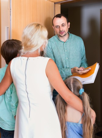 confiscation: Serious collector trying to collect debt from  family with children standing on doorstep