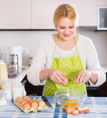 omlet: Smiling housewife making dough with eggs and milk in kitchen