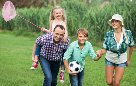 freetime activity: Positive family of four spending summer day in activity at countryside