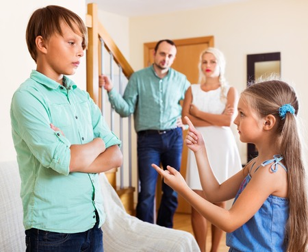 brother sister: Girl talking with his brother in  presence of parents